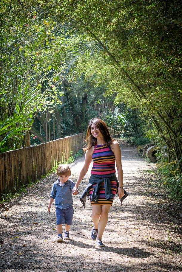 Mãe passeia com o filho em estradinha de terra com folhagem de bambu