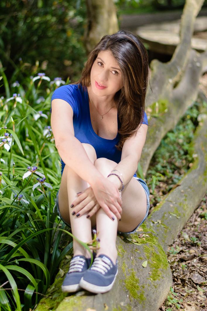 Sentada abraçando as pernas