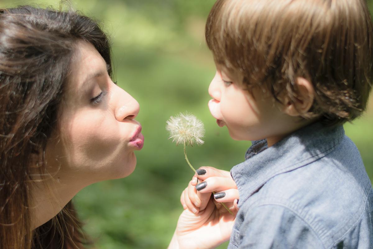 Mãe e filho soprando dente de leao