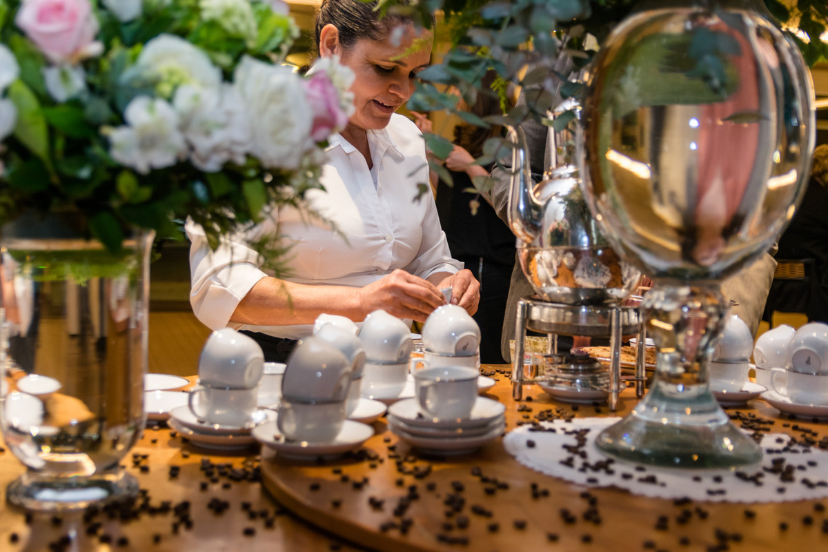 Atendente serve café aos convidados na saída do evento.