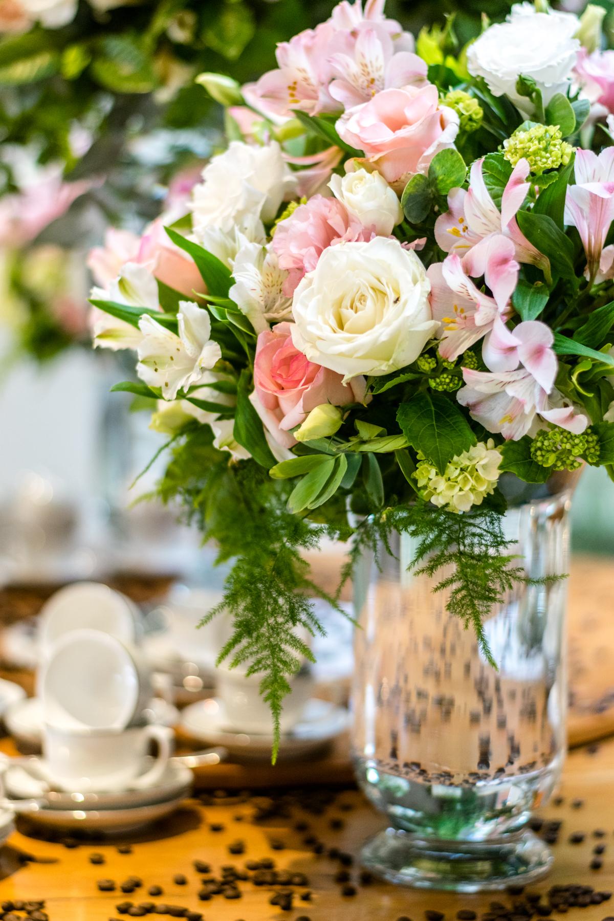 Em destaque o lindo arranjo de flores da mesa do café