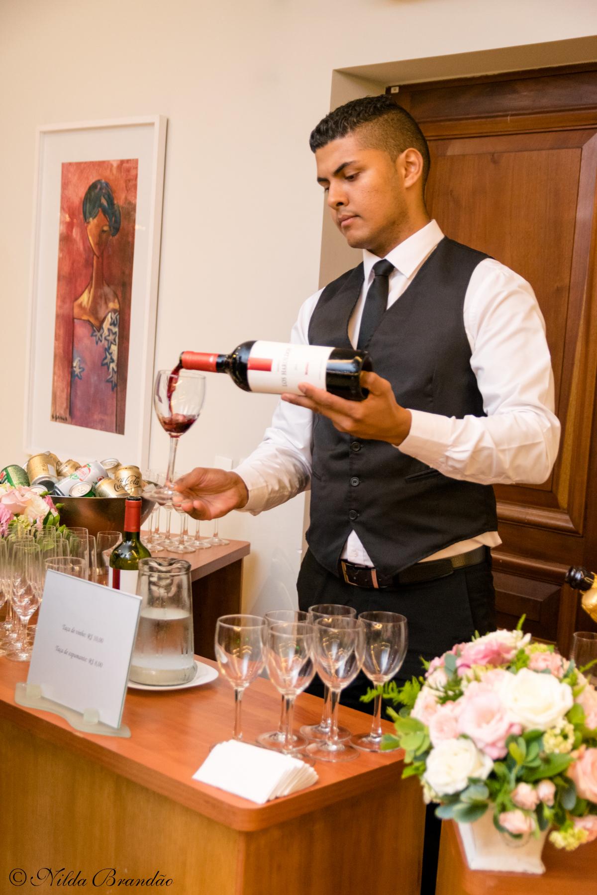 Garçon serve vinho
