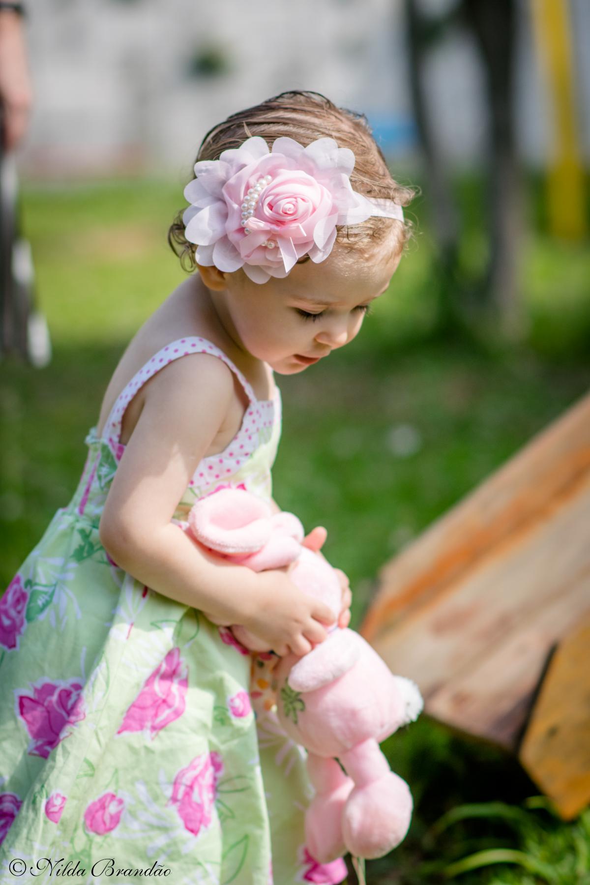 Aniversariante brincando com seu coleho de pelucia no jardim de casa.