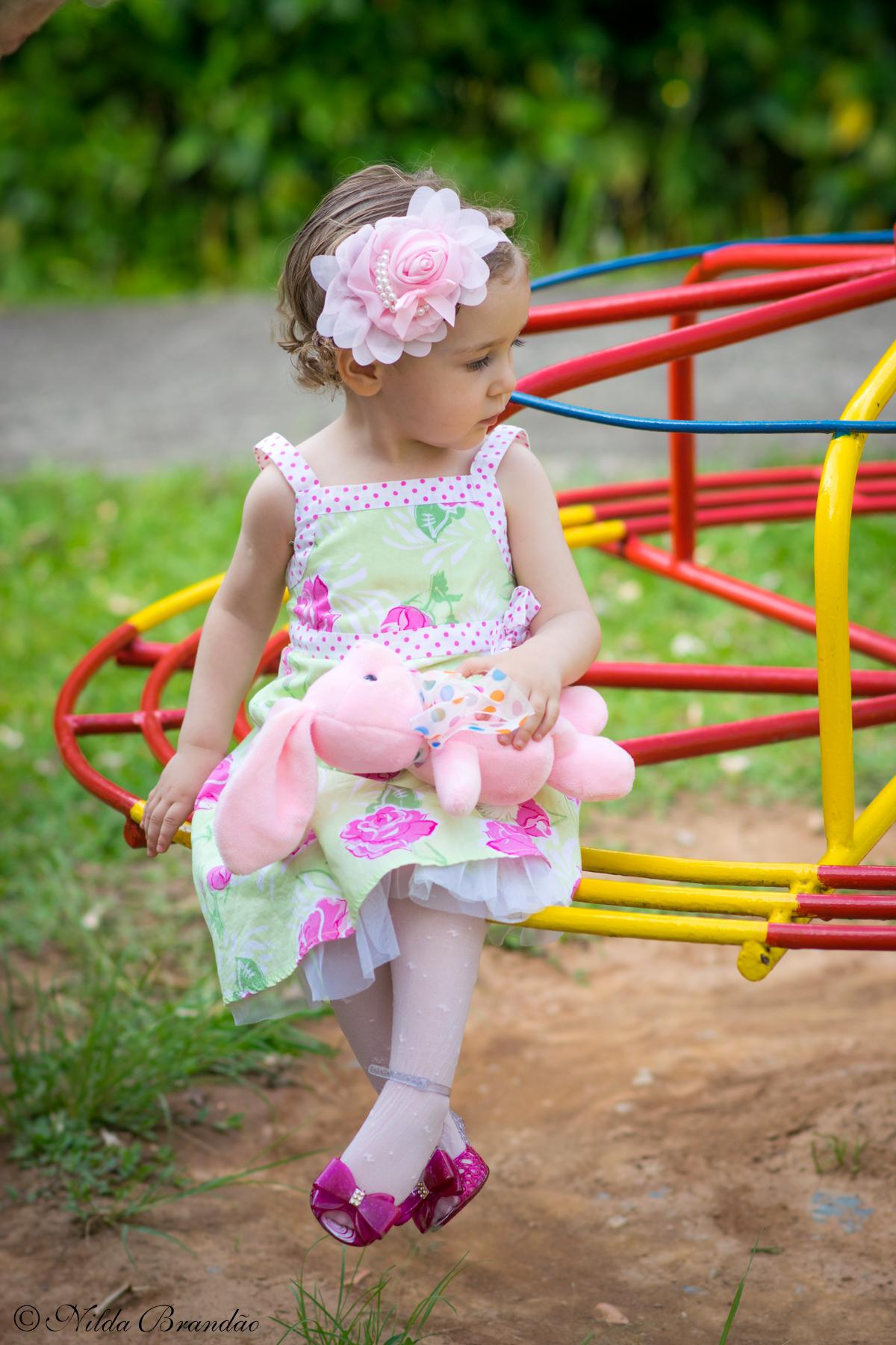 Menina sentada no brinquedo com seu coelhinho no colo usando um lindo enfeite de cabelo.