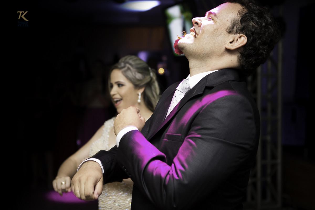 Foto do casal durante a dança. Momento divertido em que o noivo está com uma rosa na boca.