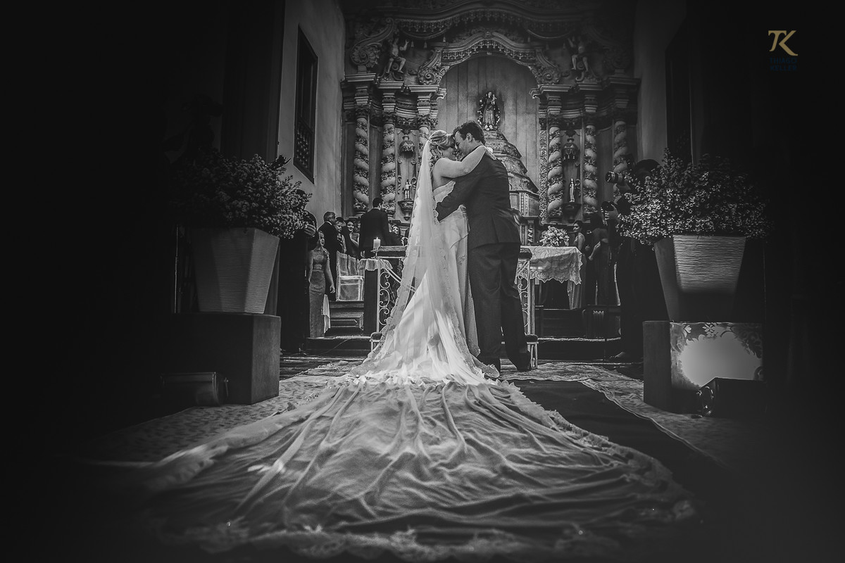 Foto em preto e branco ao final da cerimônia de casamento. Noivo e noiva dão o seu primeiro beijo casados.