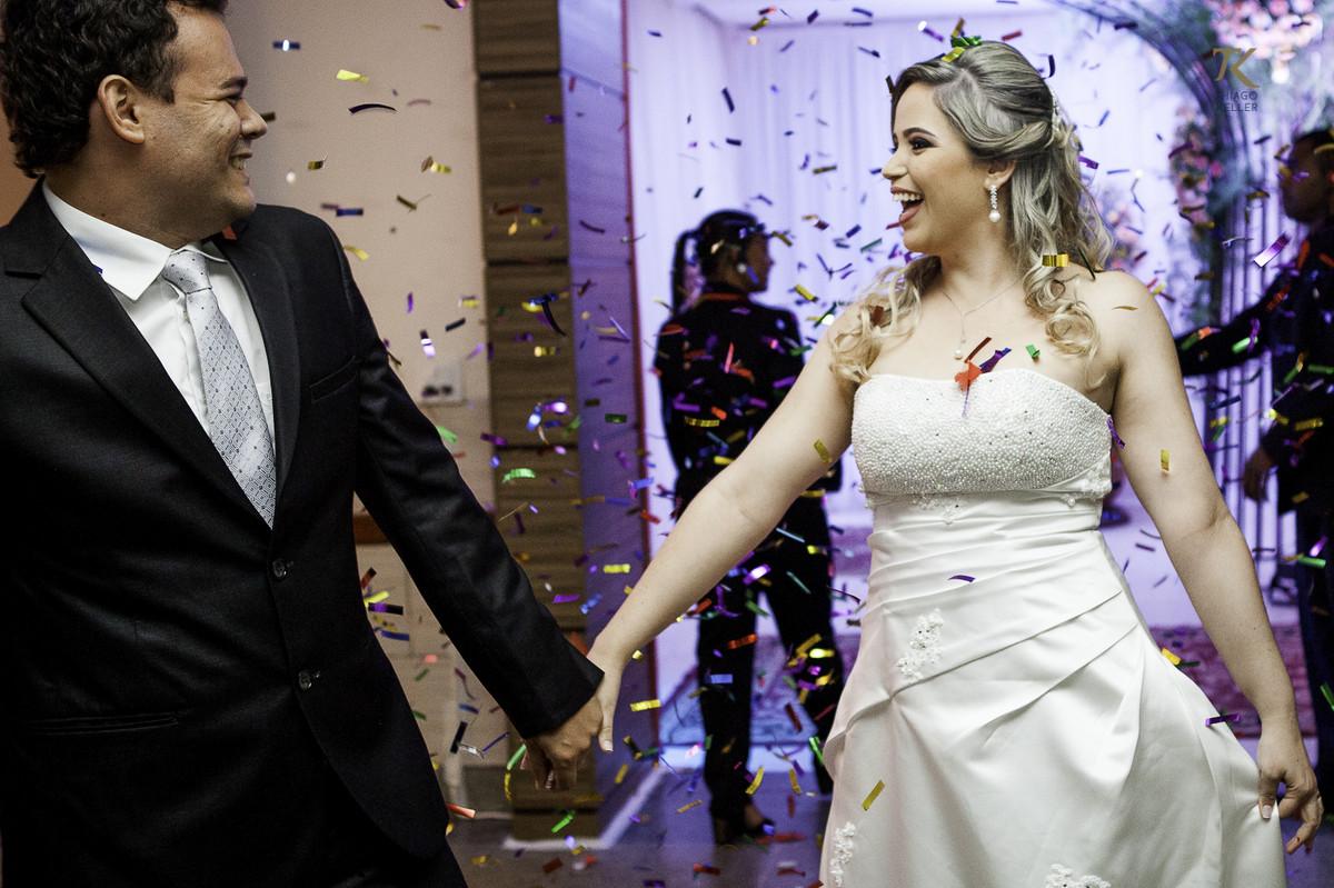 Noivo e noiva entram na festa felizes, com confetes. Foto divertida e leve.