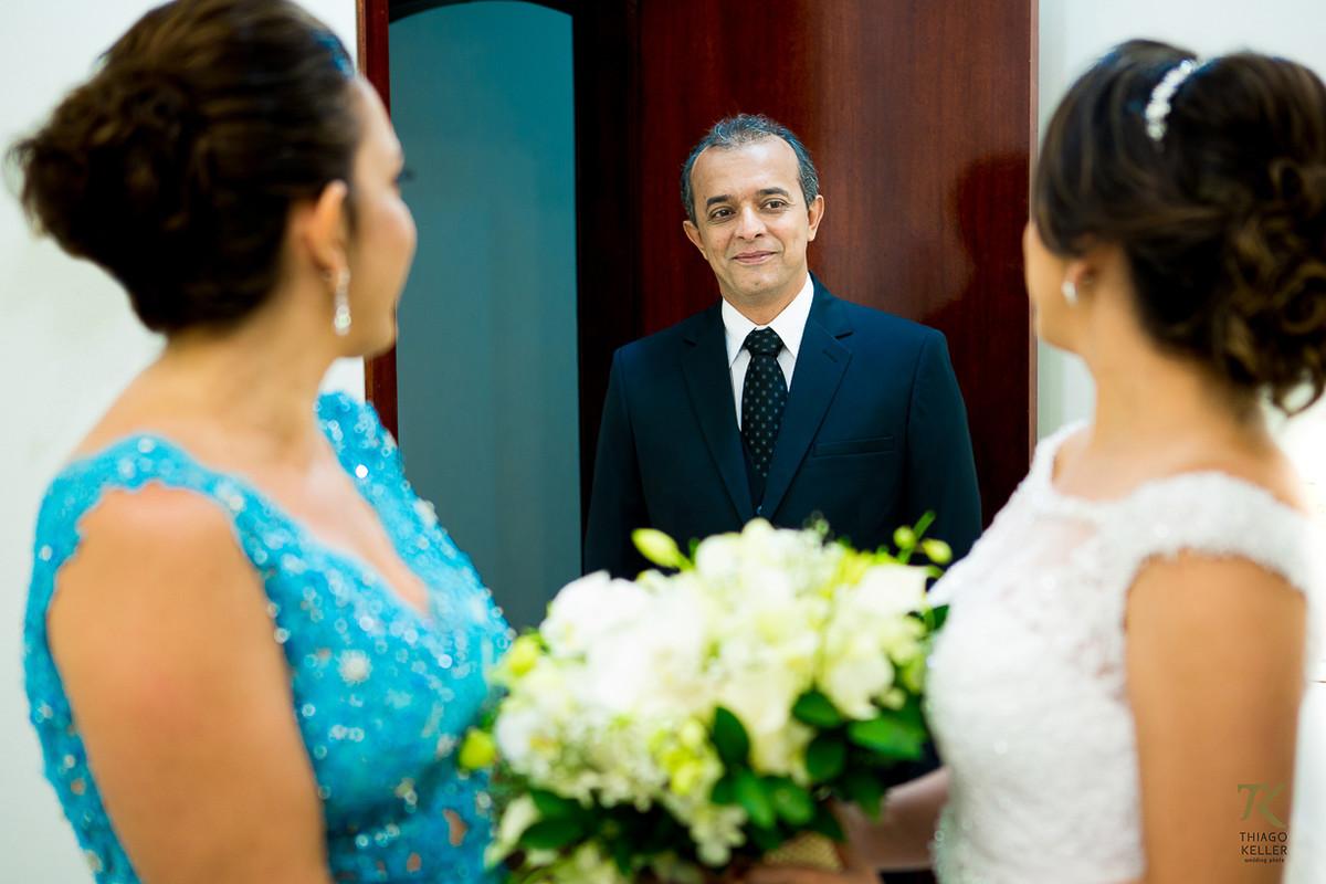 Foto antes do casamento com a mãe e o pai da noiva tendo o primeiro encontro com a filha já vestida para o casamento.