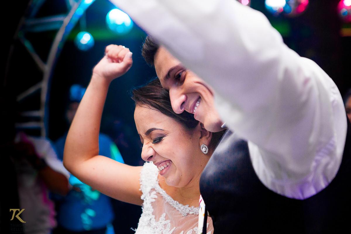 Foto dos noivos se divertindo durante a festa realizada no salão do Jóquei Clube.