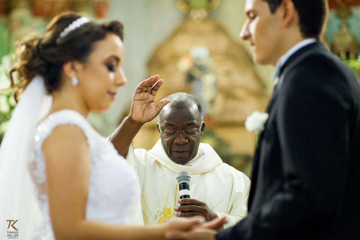 Foto do padre abençoando o casal em frente ao alta da Igreja do Rosário.