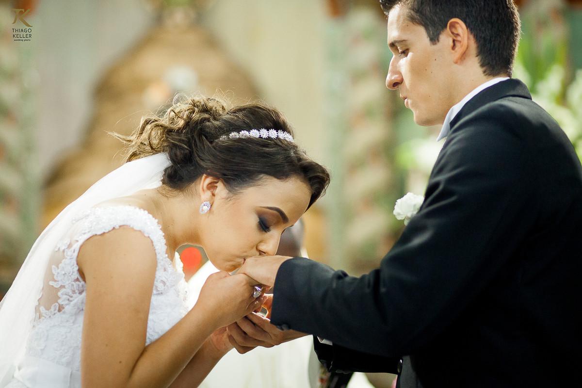 Foto da noiva beijando a aliança do noivo em frente ao alter da Igreja do Rosário.
