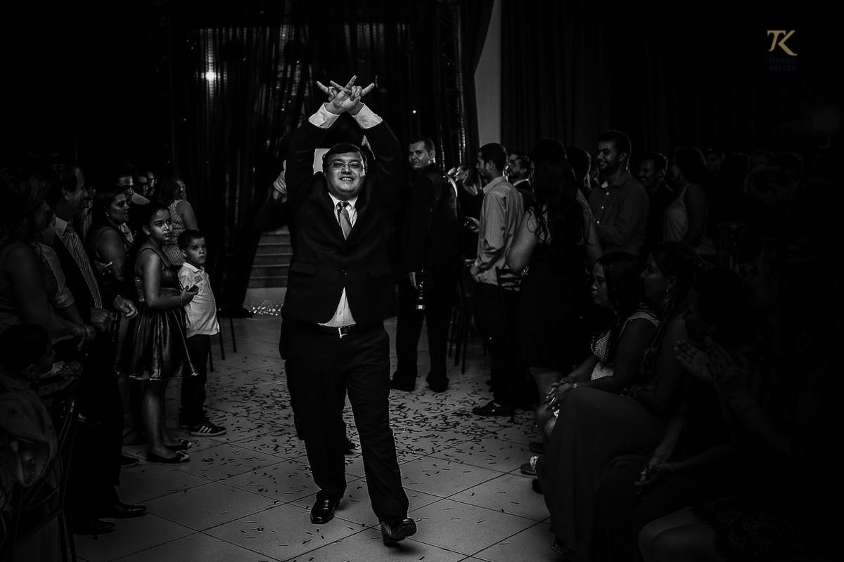 Foto de formatura realizada na cidade de Cristalina, Goias. Formando fazendo o sinal do metal. Foto em preto e branco.