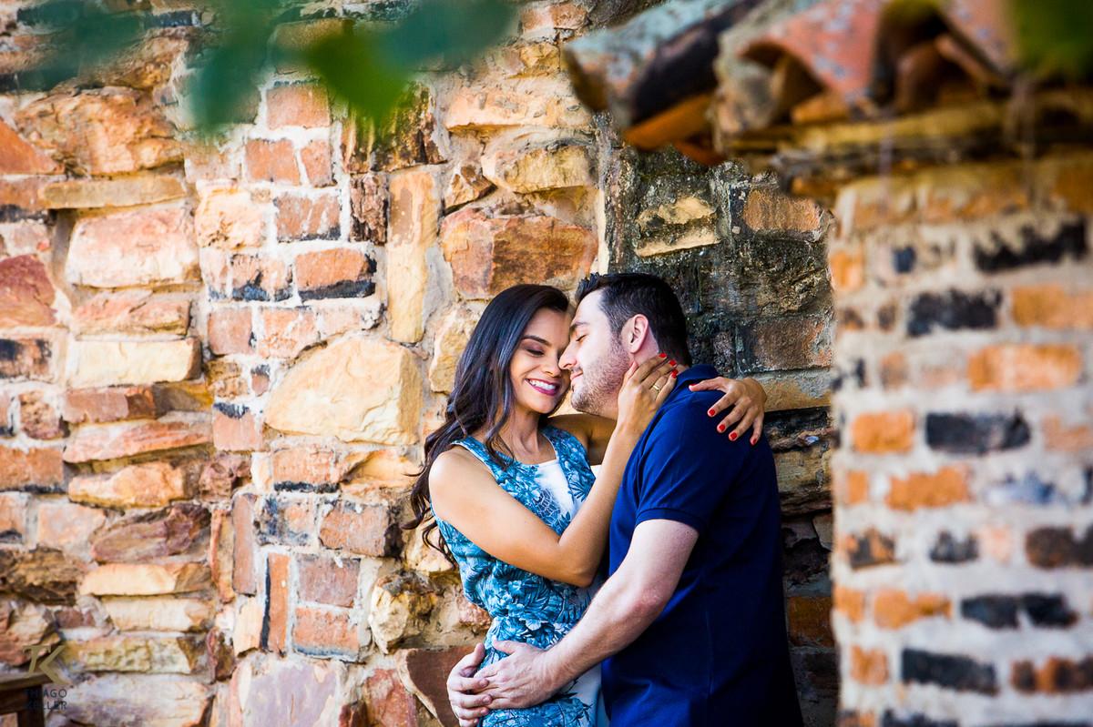 Casal apaixonado namora encostado em muro depedra