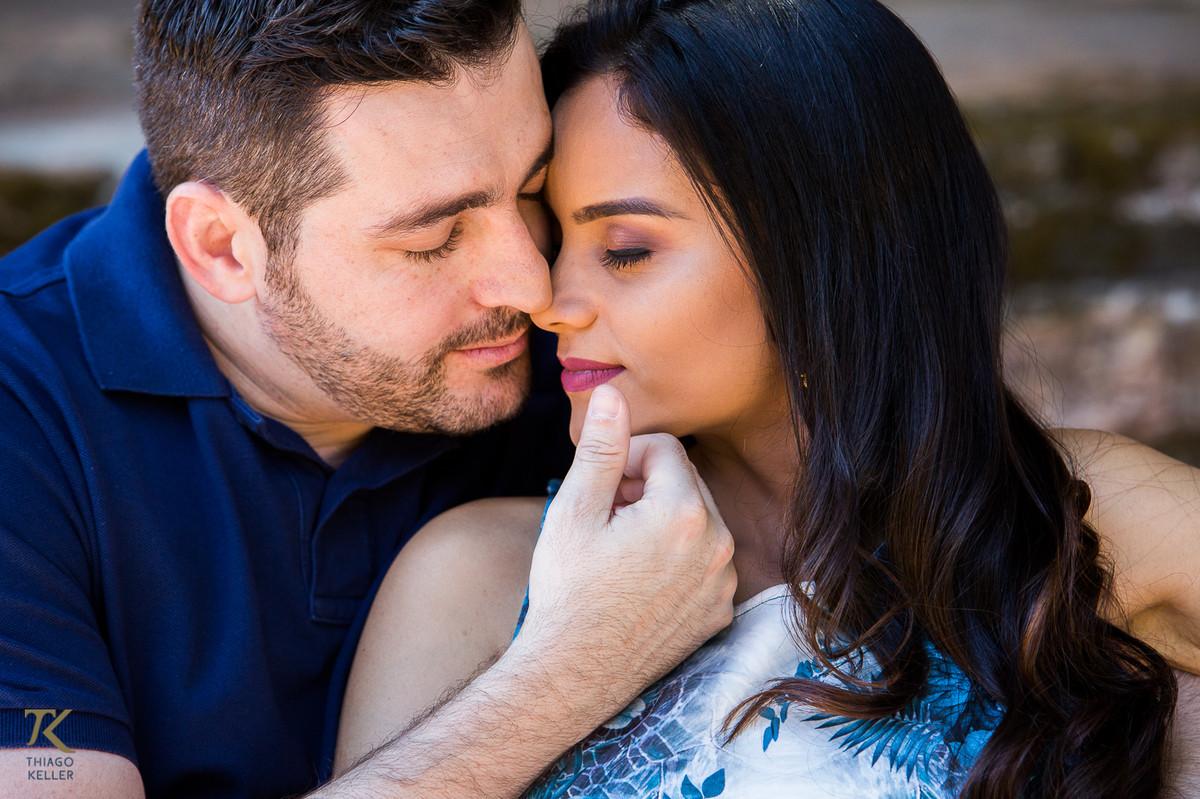 Casal apaixonado está sentado e o homem faz carinho no rosto da mulher com a mão
