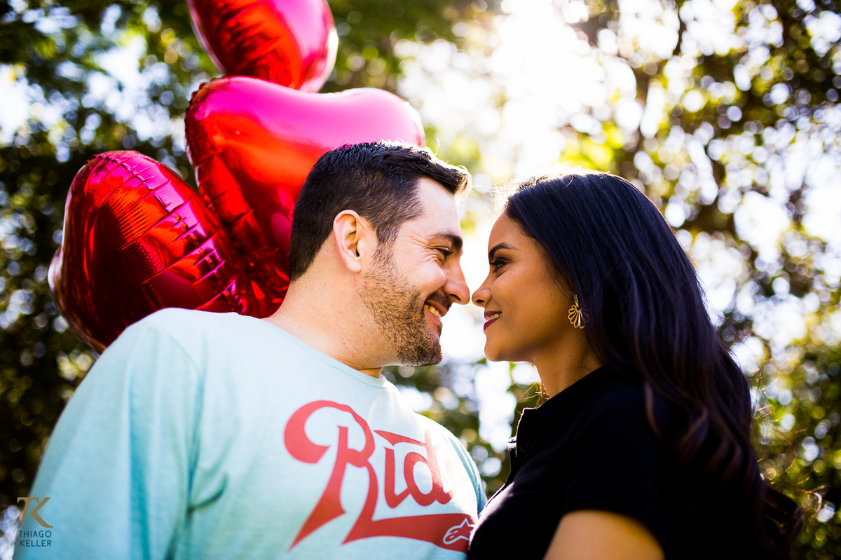 Casal apaixonado se olha segurando balões de coração