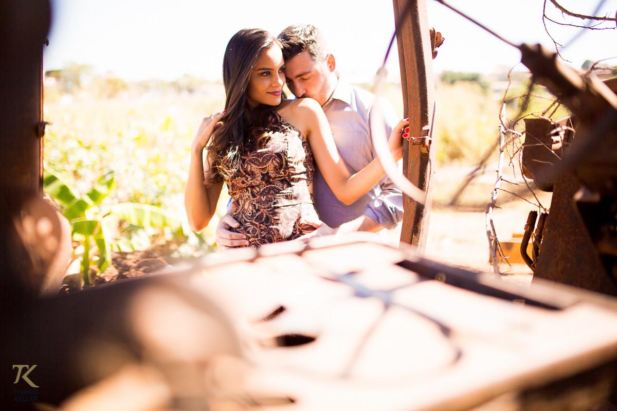 Casal apaixonado se abraça e o homem beija o ombro da mulher