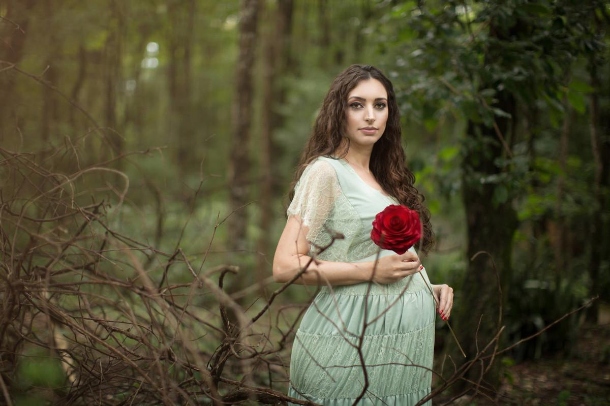Grávida segurando flor vermelha na floresta verde. Fotografada pelo fotógrafo de gestante Rafael Ohana em Brasília-DF.
