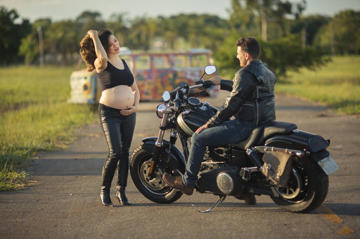 Grávida fazendo charme pro seu esposo motociclista. Foto feita pelo fotografo de gestantes Rafael Ohana em Brasília-DF