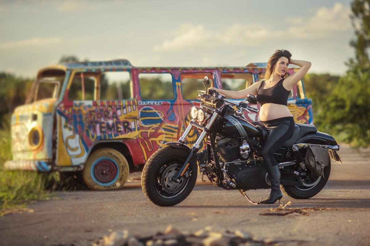 Gestante fazendo charme em cima de moto Harley Davidson. Foto feita pelo fotografo de gestantes Rafael Ohana em Brasília-DF