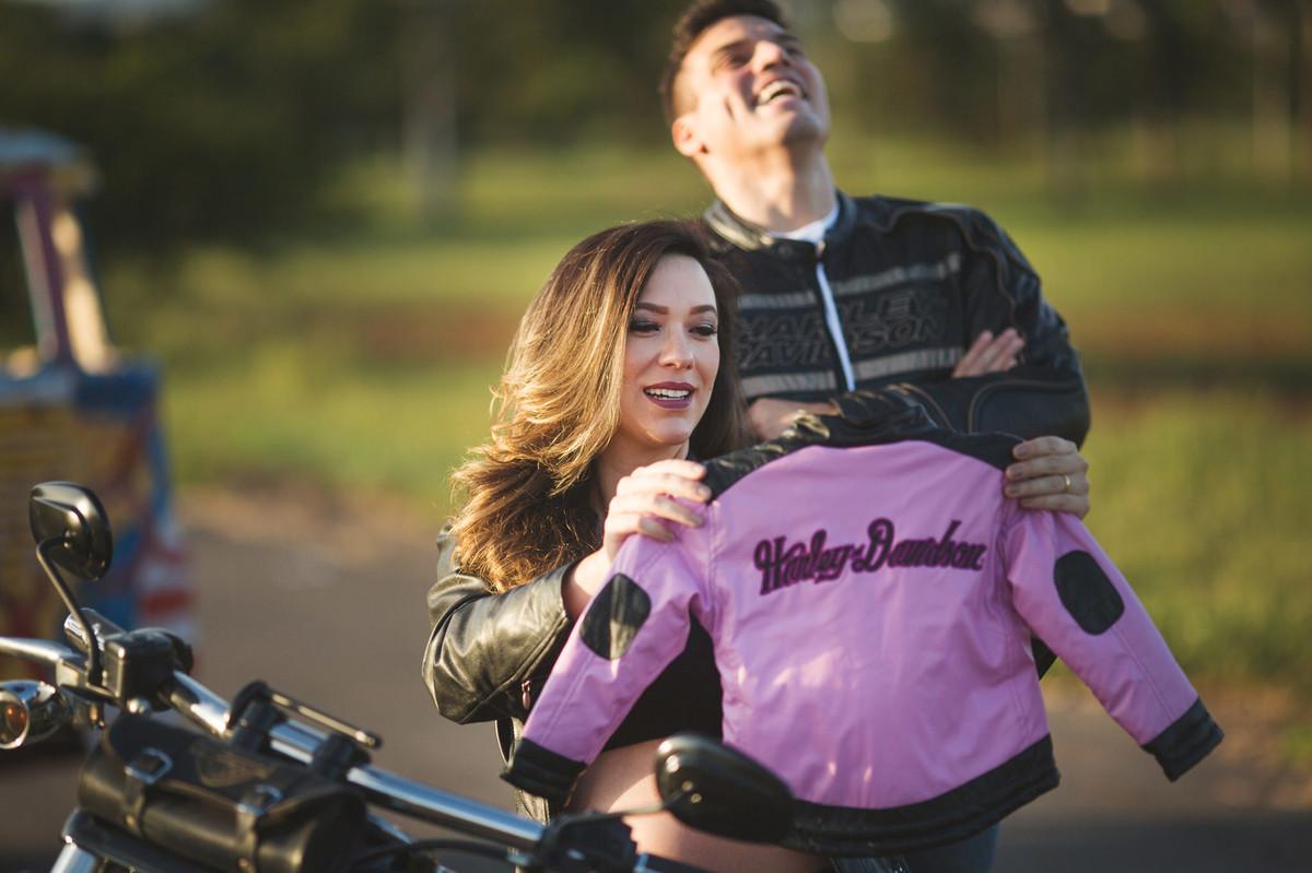 Gestante olhando jaqueta de couro da filha que vai nascer enquanto seu marido dá risadas. Foto feita pelo fotografo de gestantes Rafael Ohana em Brasília-DF