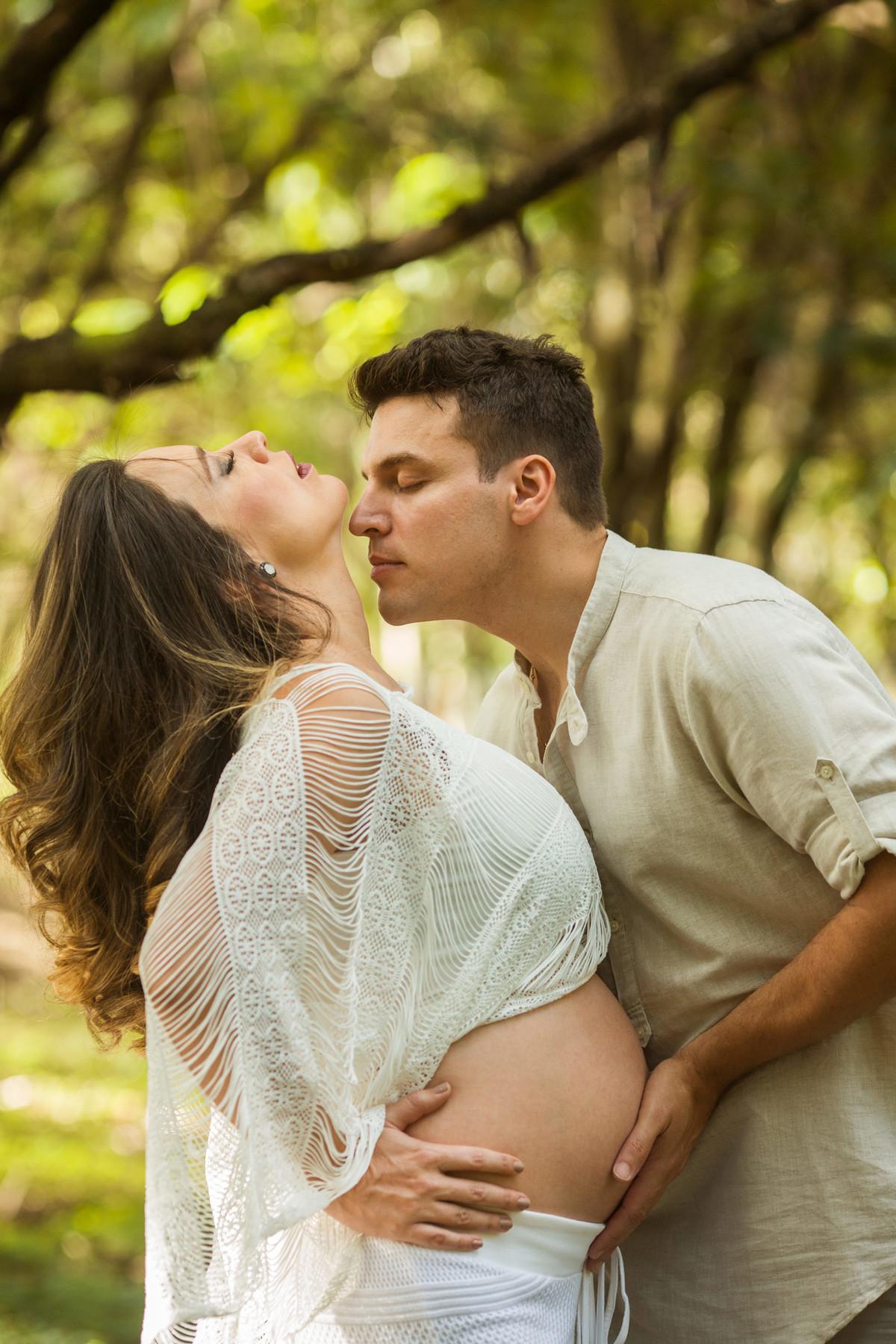 Marido beijando esposa grávida na floresta. Foto feita pelo fotografo de gestante Rafael Ohana em Brasilia-DF