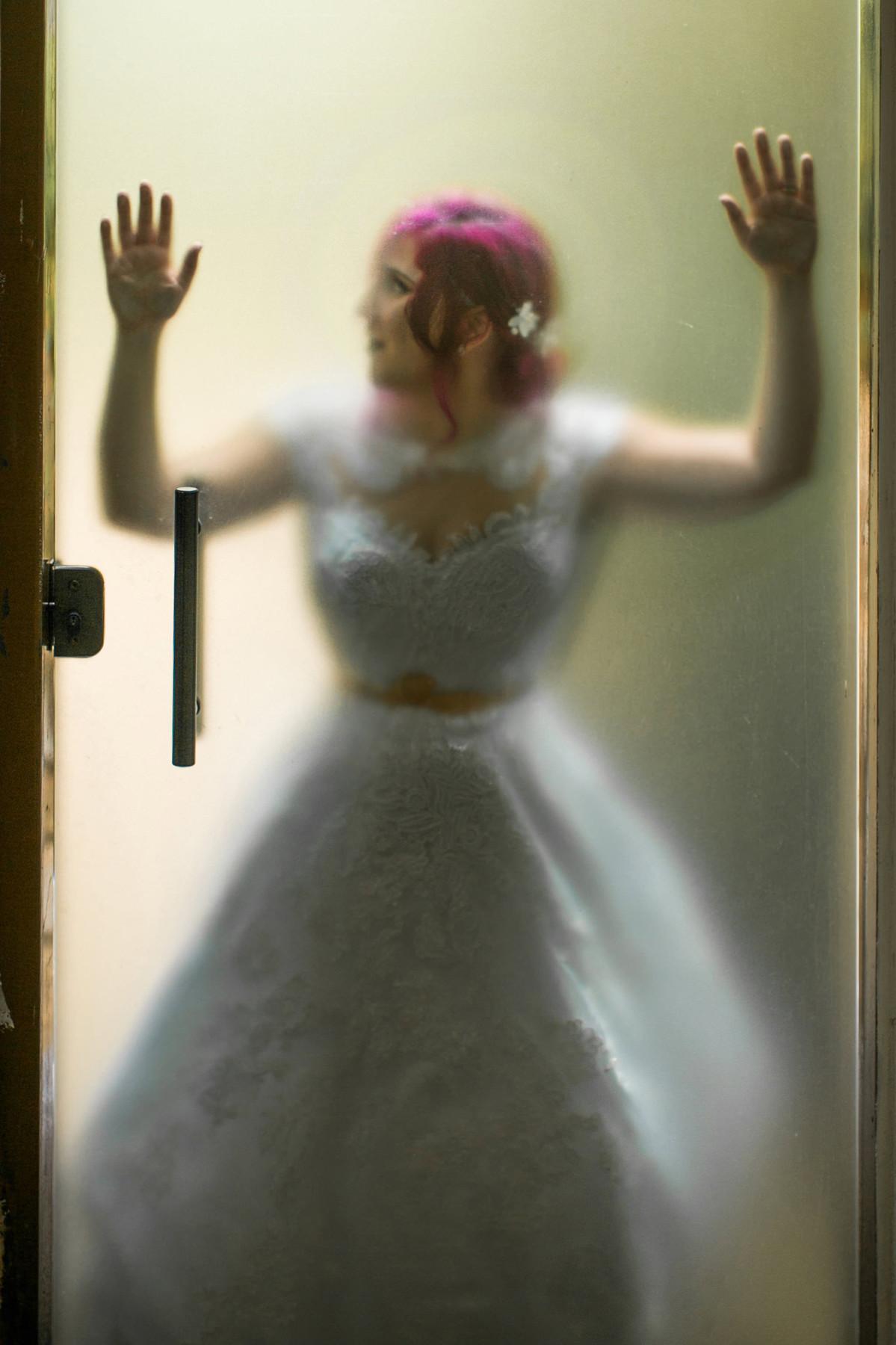Noiva apoiada em vidro transparente