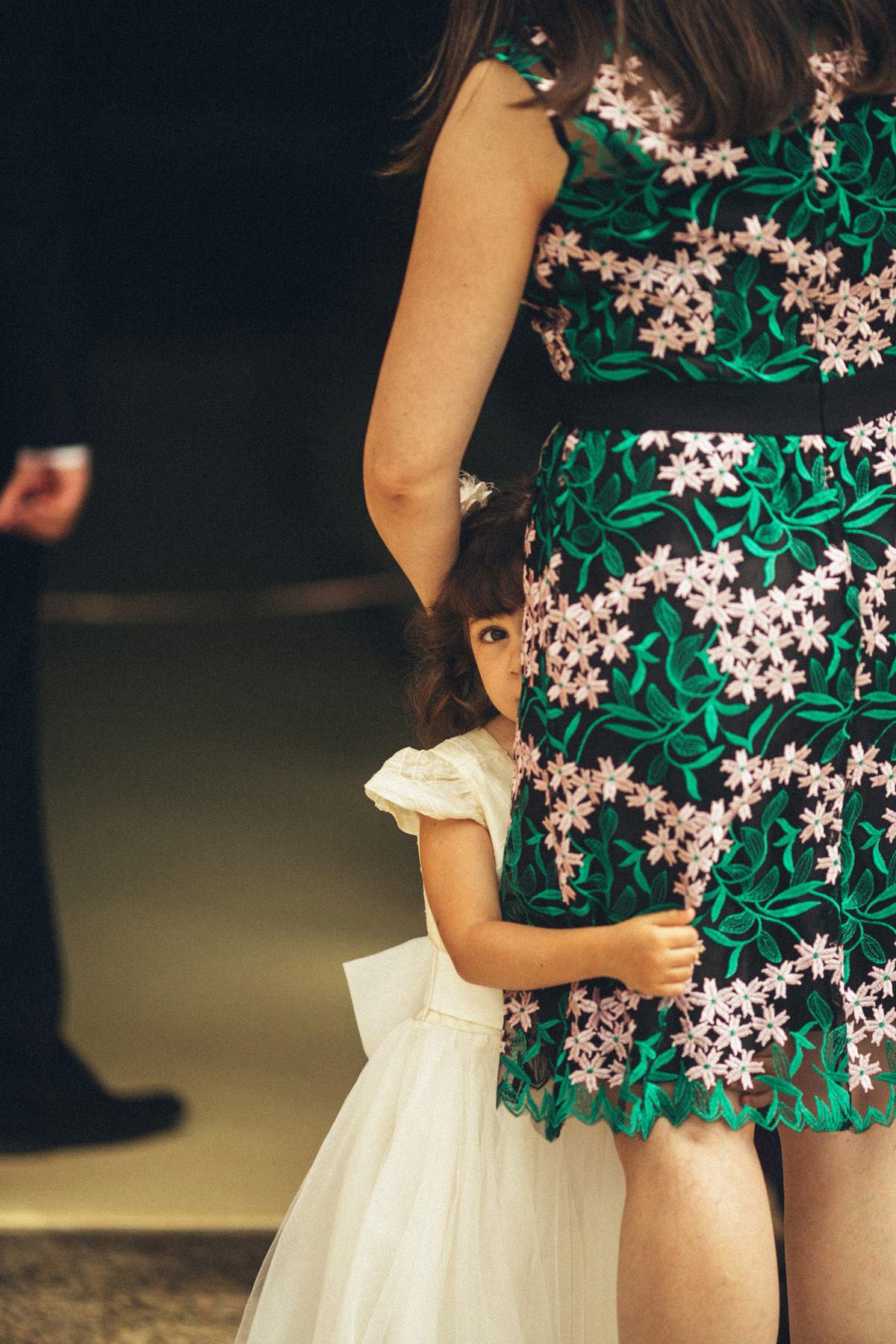 Menina se escondendo atrás da saia da mãe