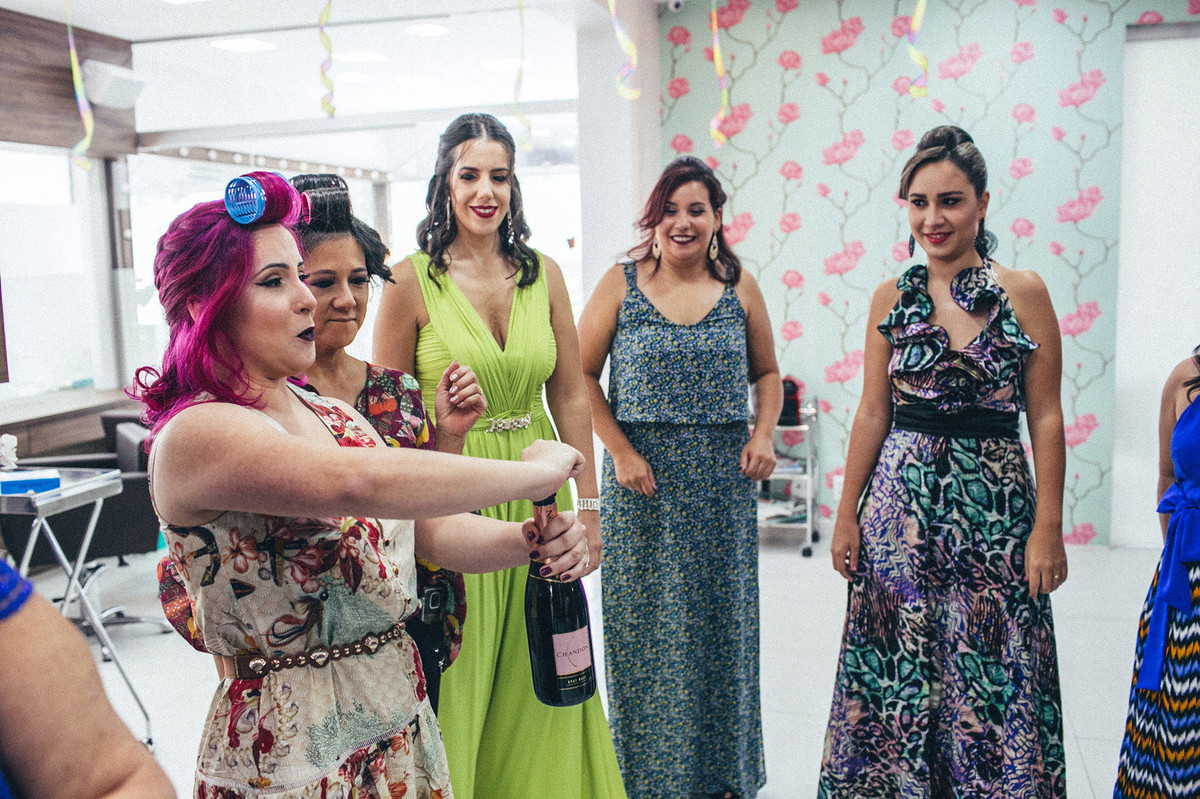 Noiva abrindo espumante em seu making of com as madrinhas do seu casamento