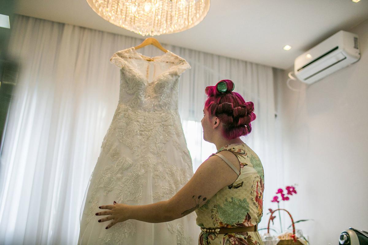 Noiva olhando seu vestido de noiva