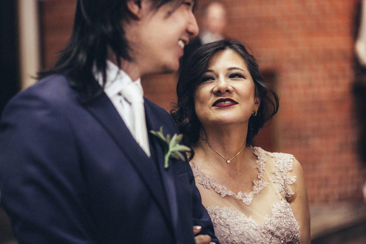 Mãe do noivo olhando pra ele com cara de orgulho.