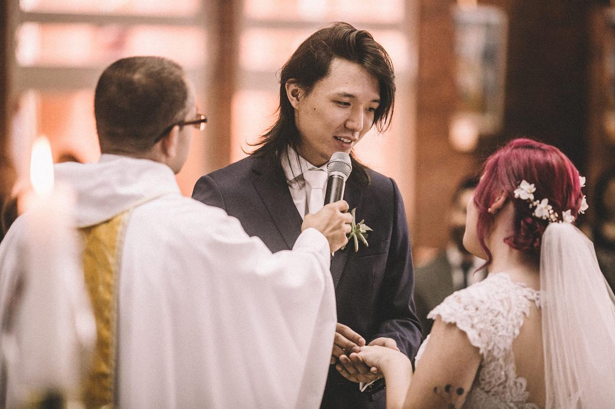 Noivo colocando aliança de casamento no dedo da noiva em Paróquia São Camilo de Lellis