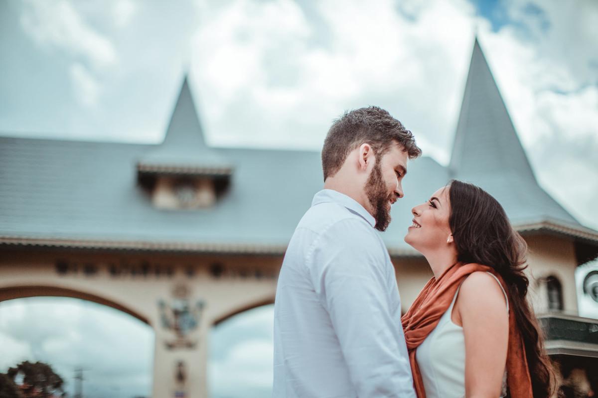 Casal se olhando no pórtico de Gramado-RS. Foto feita pelo fotógrafo de casamento Rafael Ohana.