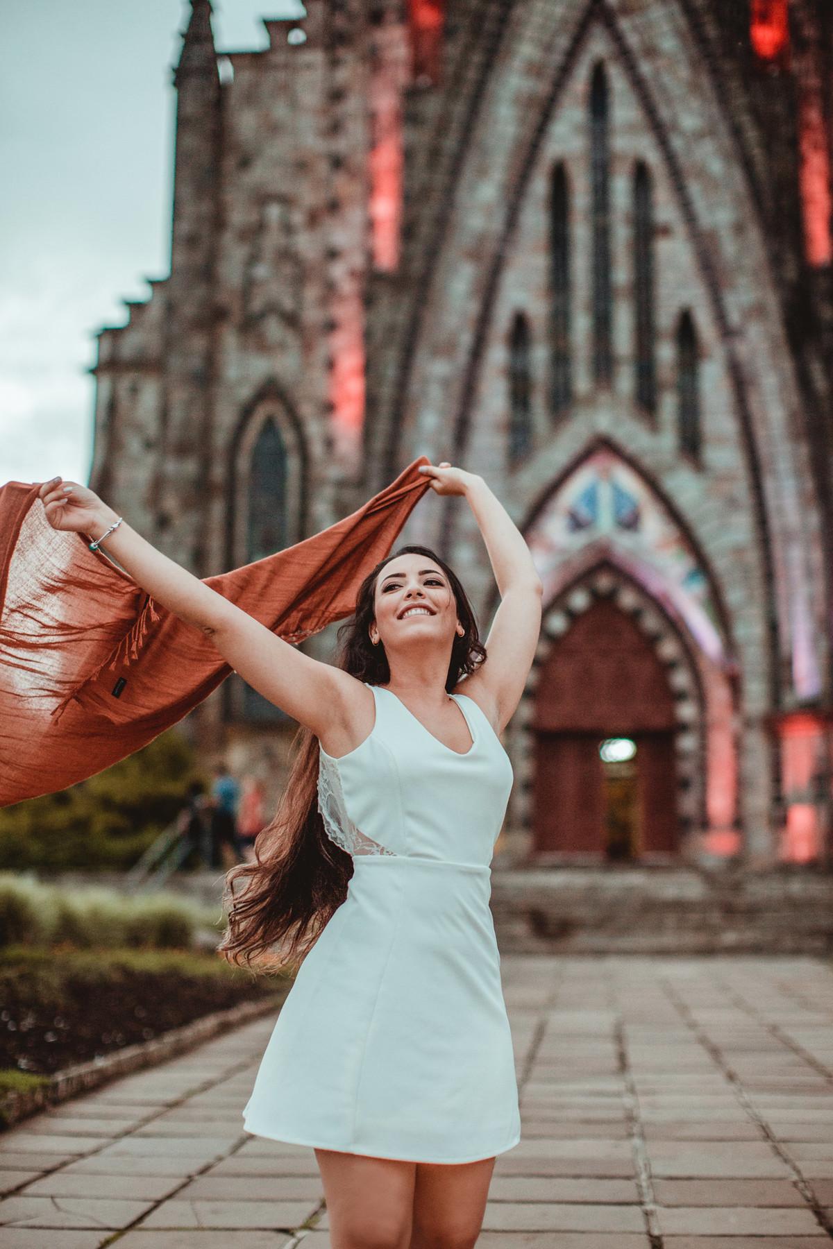 Noiva se divertindo na frente de igreja matriz de Canela-RS. Foto feita pelo fotógrafo de casamento Rafael Ohana