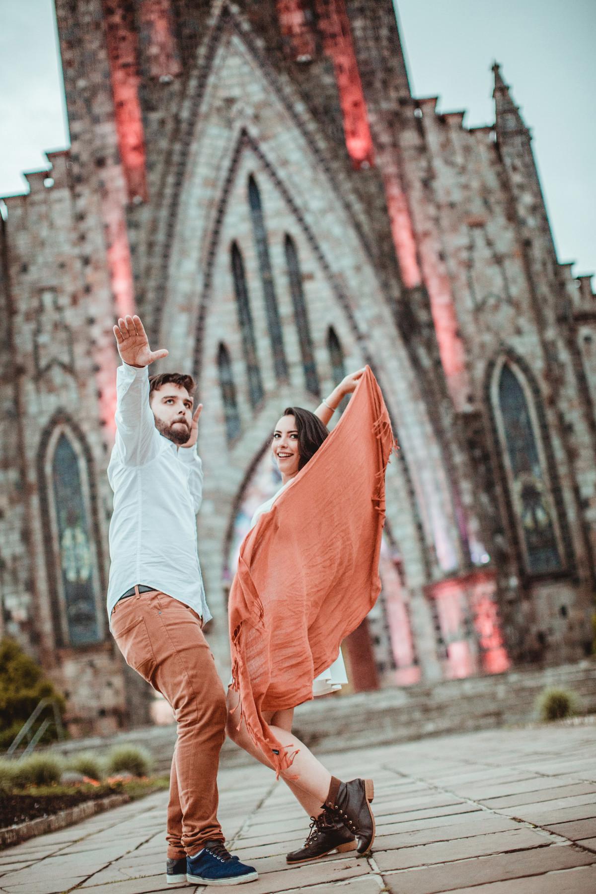 Casal se divertindo em ensaio romântico em frente a Igreja Matriz de Canela-RS. Foto feita pelo fotógrafo de casamento Rafael Ohana