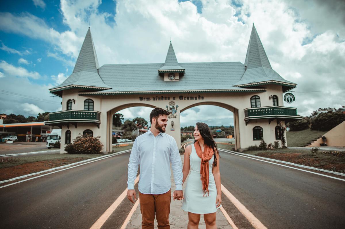 Casal se olhando de mãos dadas em pórtico de Gramado-RS. Foto feita pelo fotógrafo de casamento Rafael Ohana