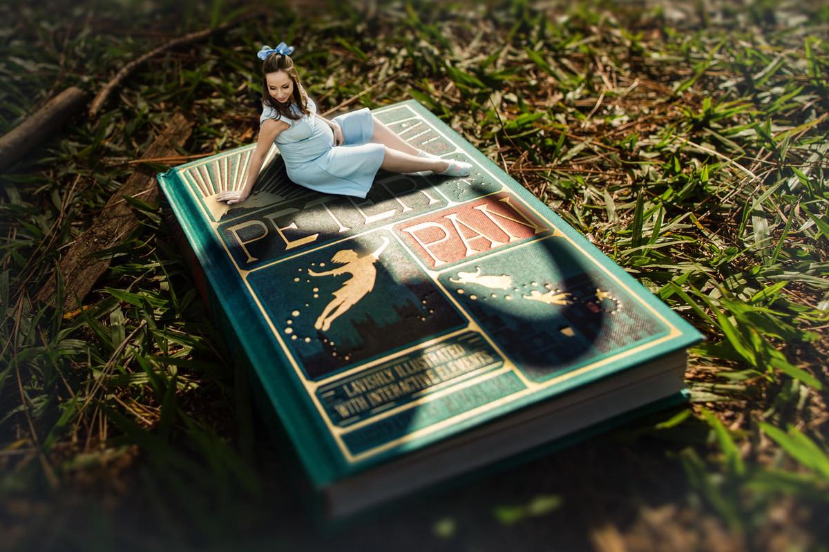 Ensaio de grávida na temática mundo Terra do Nunca feito pelo fotógrafo Rafael Ohana em Brasiilia-DF Wendy em miniatura em cima do livro do Peter Pan