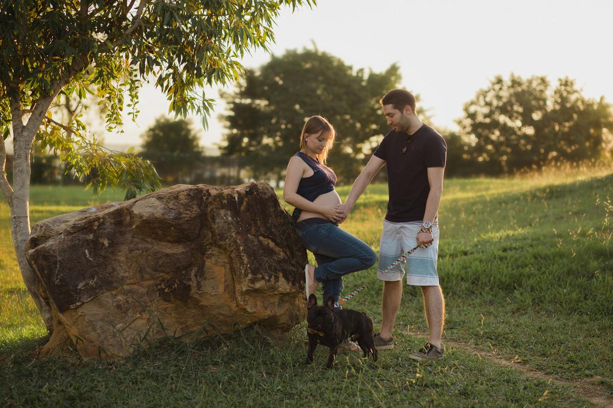 Ensaio de família feito no Lago Norte. Grávida apoiada em pedra com cachorro.