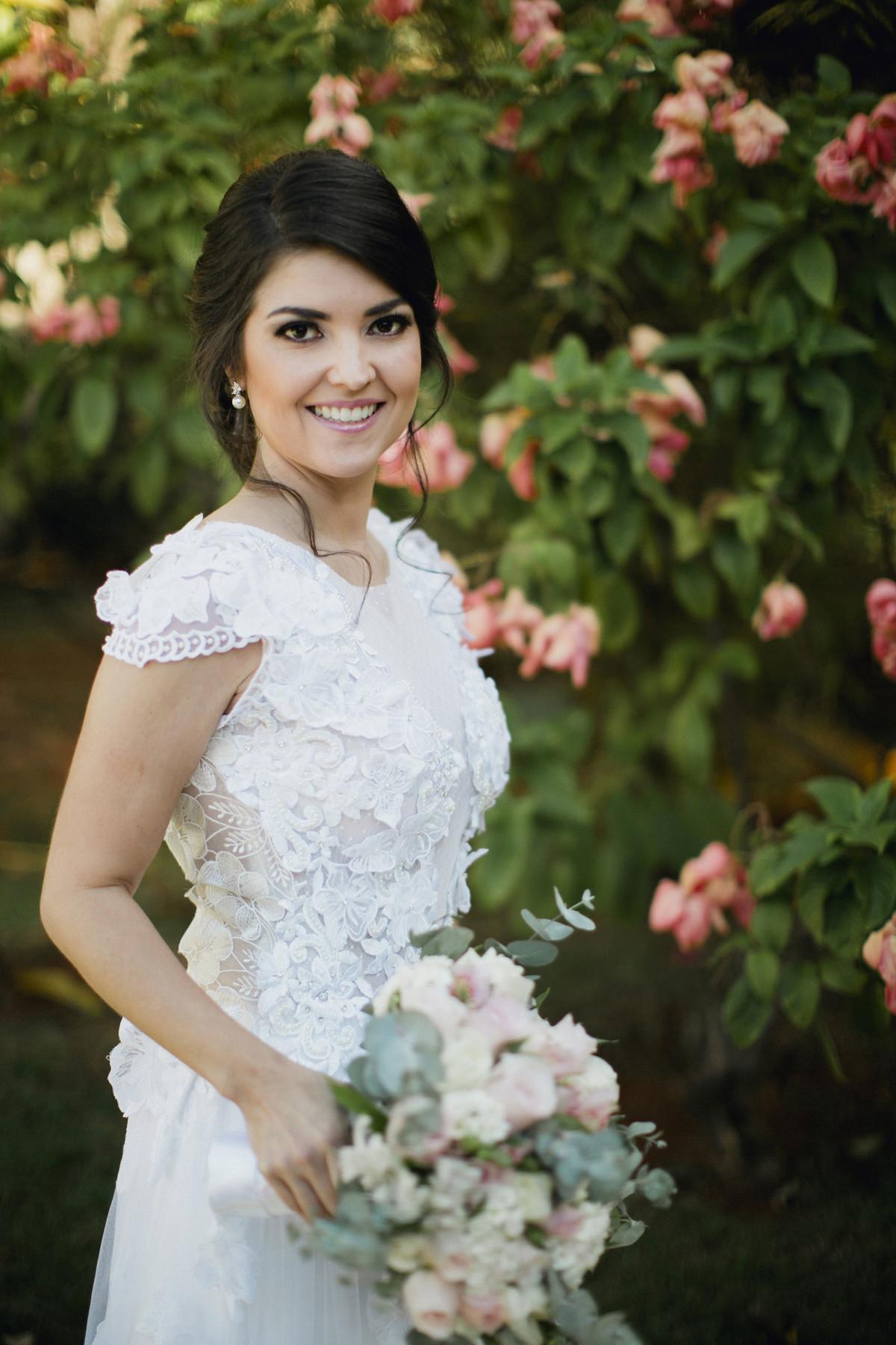 Noiva posando perto de flores rosas
