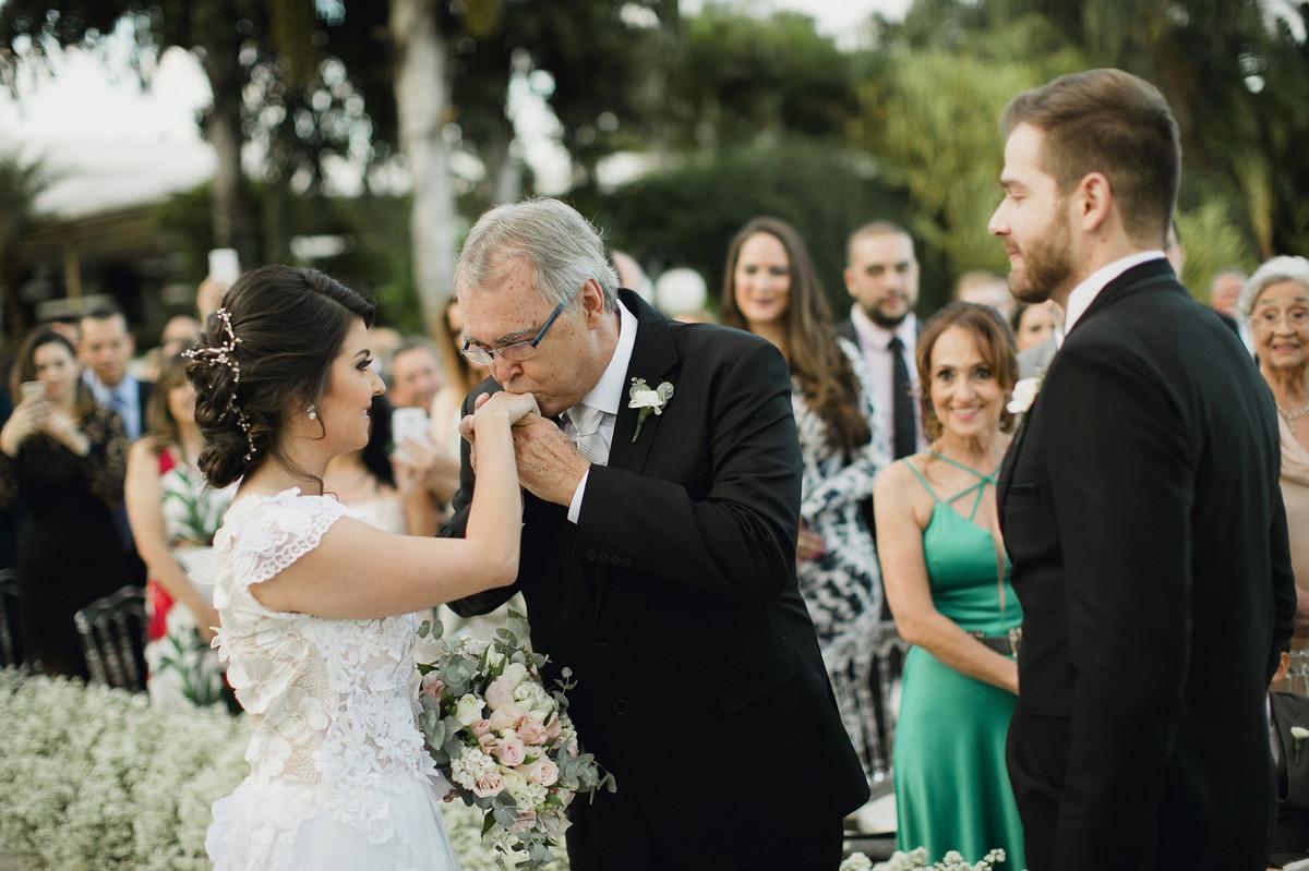 Pai da noiva se despedindo da noiva beijando sua mão