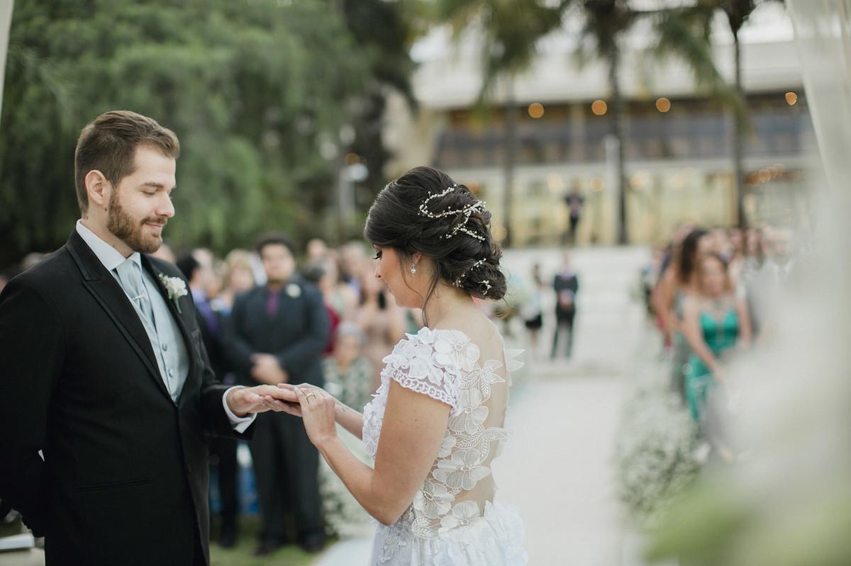 Noiva colocando a aliança no dedo do noivo