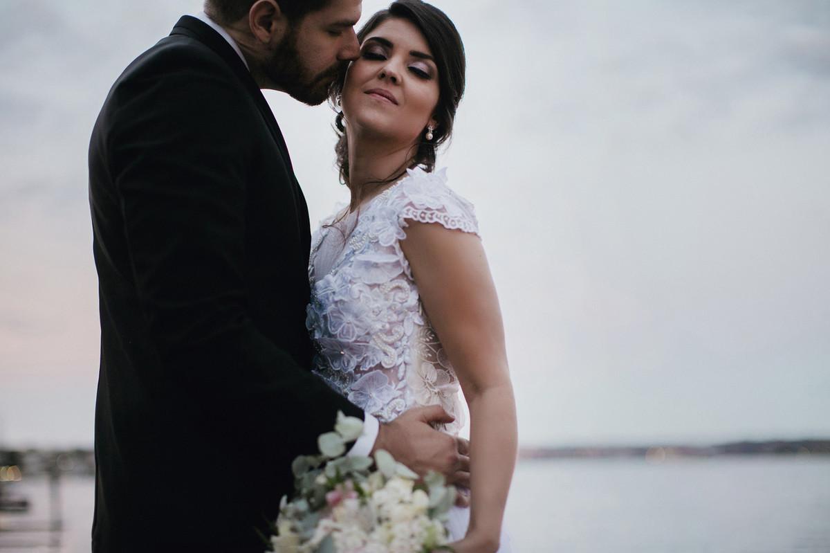 Noivo beijando bochecha da noiva perto do lago
