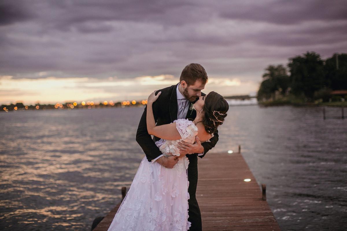 Noivos se beijando no lago