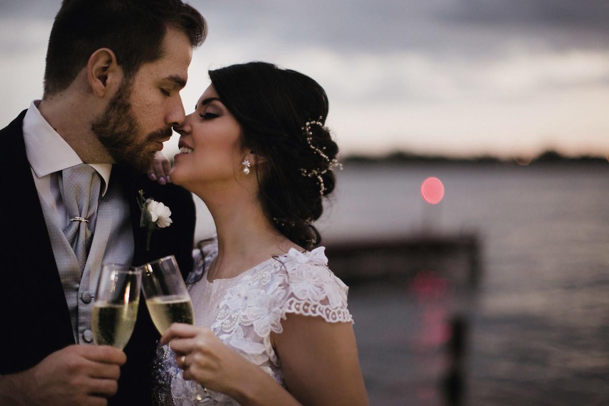 Noivos brindando com champagne na beira do lago em Porto Vittoria em Brasília-DF