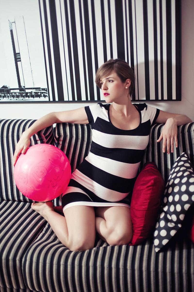 Gestante Milena sentada no sofá listrado com uma bola ensaio feito em Brasília DF