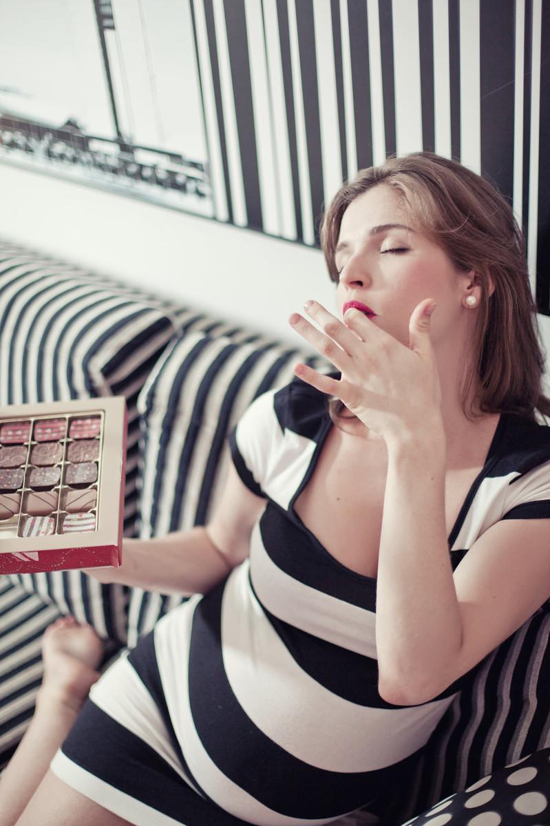 Gestante Milena sentada no sofá listrado com comendo chocolates ensaio feito em Brasília DF