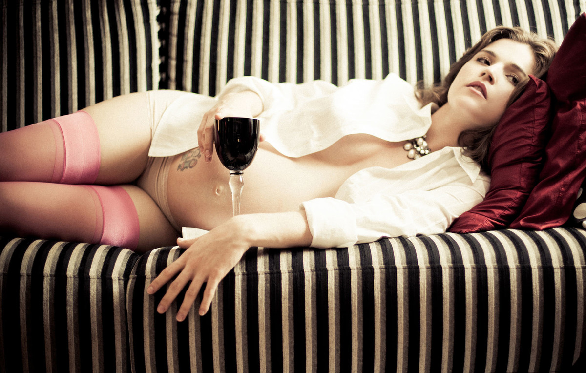 Milena grávida deitada no sofá listrado com amor tomando vinho ensaio feito em Brasília DF