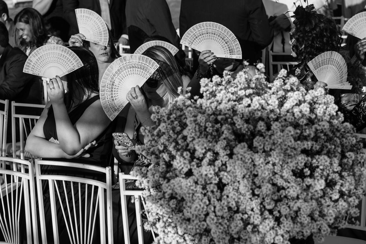 Convidados se protegendo do Sol com leques de madeira