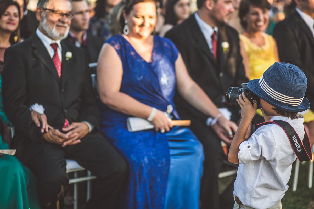 Ceriônia de casamento de Ana e Celo em Brasília-DF registrado pela equipe de Rafael Ohana Photography menino tirando fotos dos convidados