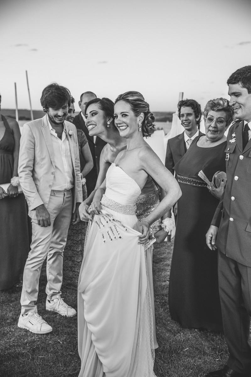 Noiva mostrando os nomes das solteiras na barra do vestido