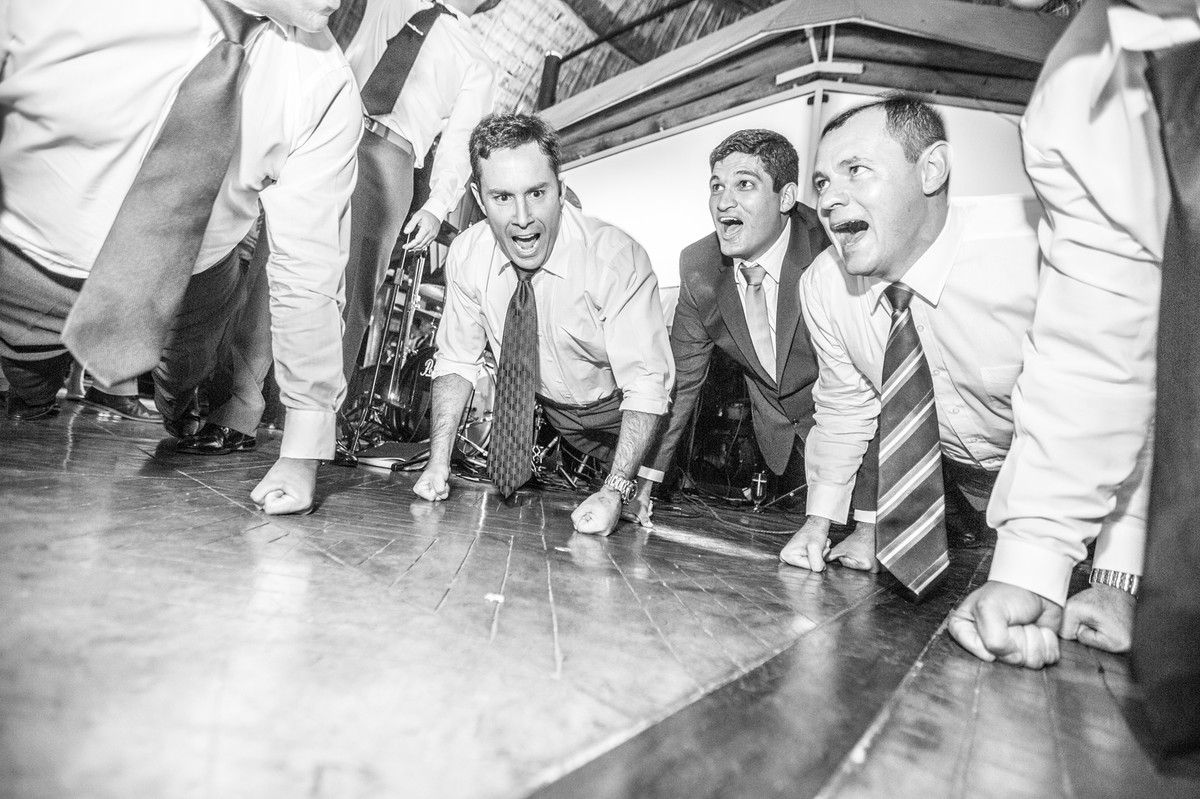 noivo e amigos fazendo flexão durante recepção de casamento
